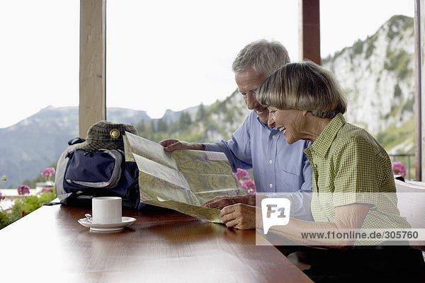 Älteres Ehepaar sitzt in einem Restaurant und sieht sich eine Landkarte an - Berge - Idylle  fully_released