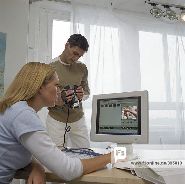 Blonde Frau sitzt vor einem Computer neben einem Mann  der sich mit einer Kamera beschäftigt - Filmen - Studio