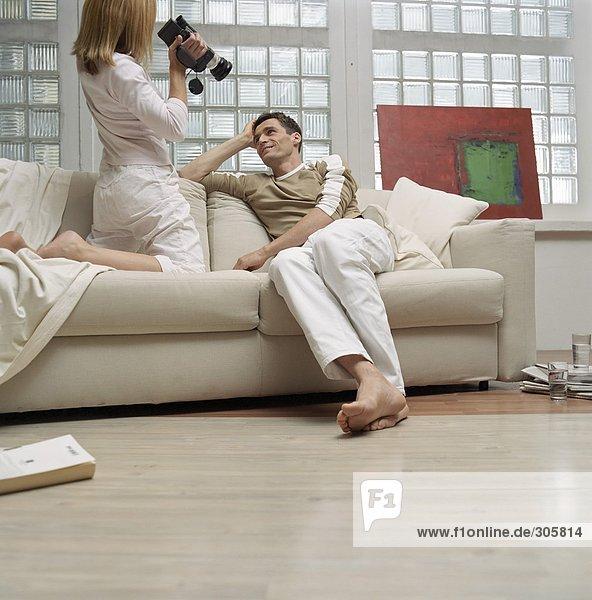 Blonde Frau filmt einen Mann auf dem Sofa - Paar - Hobby - Wohnzimmer