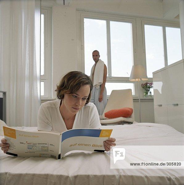 Junge Frau liegt im Bett und liest ein Handbuch über Computer - Morgens - Beziehung
