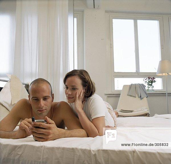 Junger Mann mit einem Handheld liegt neben einer Frau im Bett - Morgens - Technologie