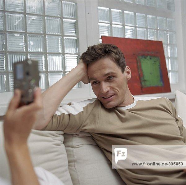 Frau fotografiert einen braunhaarigen Mann auf dem Sofa - Paar - Hobby - Wohnzimmer