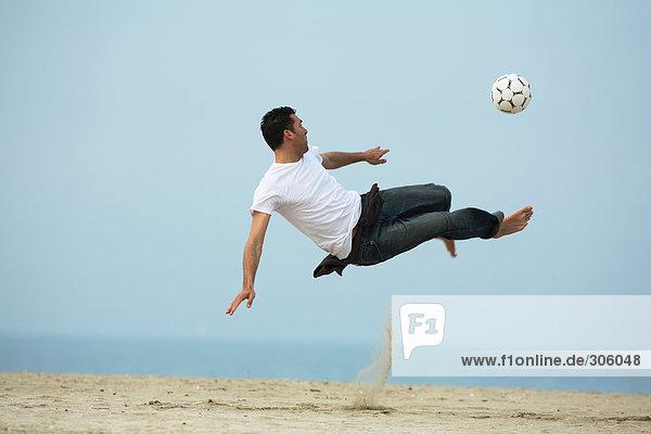 Caucasian männlichen Fußball am Strand zu üben