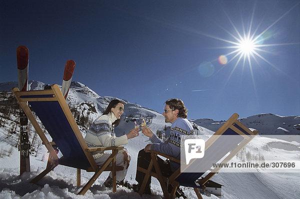 Paar auf Liegestühlen im Schnee sitzend,  Gläser haltend,  Seitenansicht