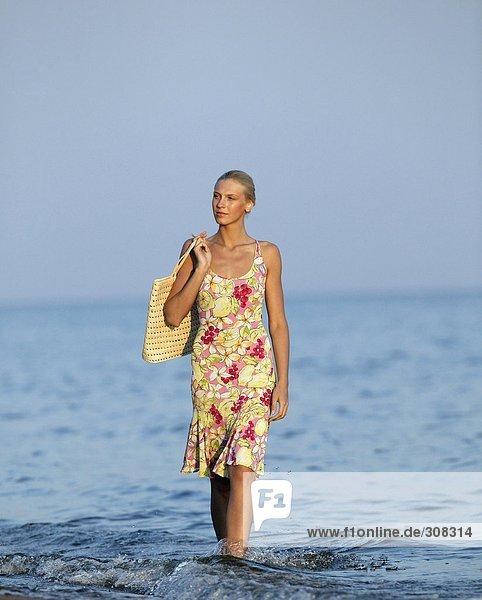 Junge Frau  die im Meer spazieren geht und wegguckt.