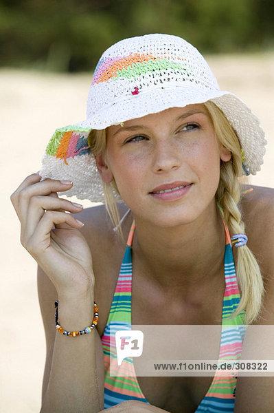 Junge Frau mit Sonnenhut am Strand  wegschauen  Nahaufnahme