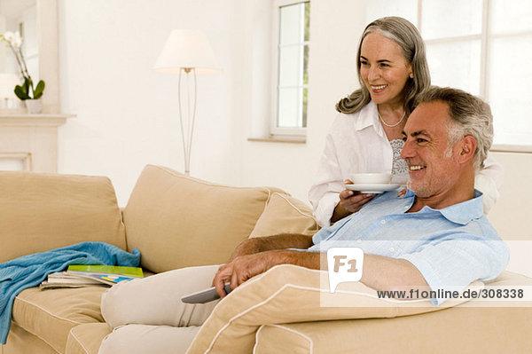 Erwachsenes Paar auf dem Sofa sitzend  fernsehend  Seitenansicht