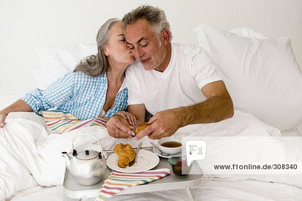 Erwachsenes Paar auf dem Bett sitzend mit Frühstück  Frauen küssen Mann