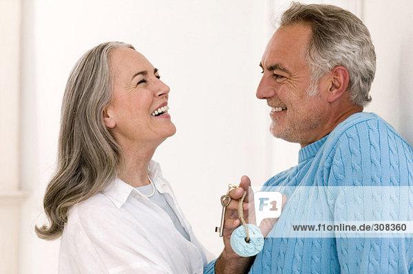Erwachsenes Paar lächelnd  Mann mit Schlüssel  Nahaufnahme