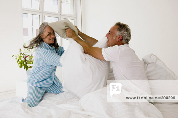 Erwachsenes Paar mit Kissenschlacht auf dem Bett