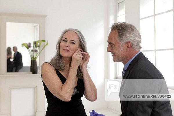 Mann  der Frauen mit begabten Ohrringen ansieht  lächelnd
