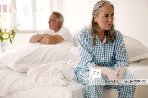 Erwachsenes Paar auf dem Bett sitzend (Fokus auf die Frau im Vordergrund)