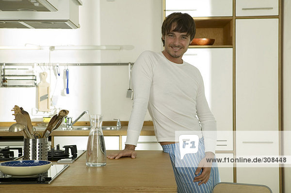 Young man standing in kitchen  smiling  portrait