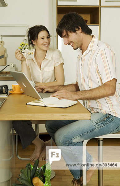 Young couple in kitchen  man using laptop  smiling