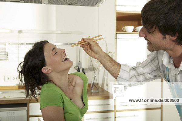 Man feeding woman with chopsticks  smiling