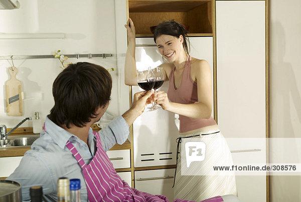 Junges Paar röstet Weingläser in der Küche  Frau lächelt
