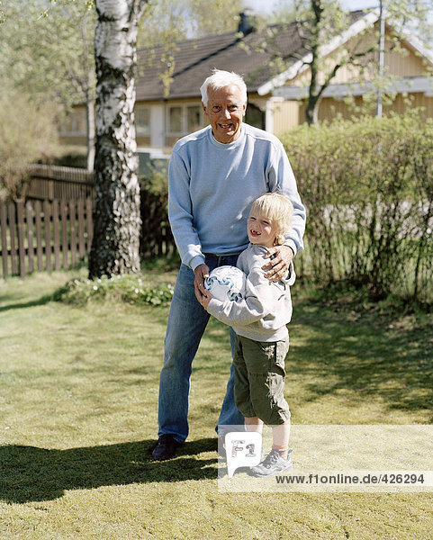 Großvater und Enkel mit einem Fußball in einem Garten.