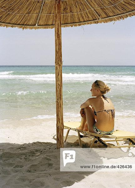 Eine Frau unter einem Sonnenschirm am Strand.