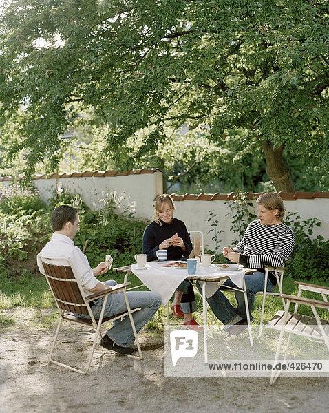 Drei Freunde Spielkarten im Freien.
