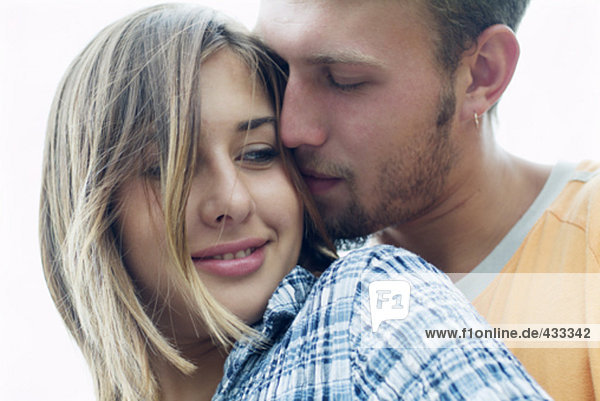 young woman being embraced by boyfriend