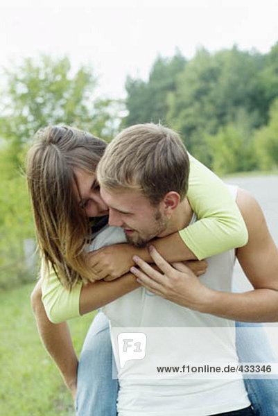 junger Mann mit seiner Freundin piggyback junger Mann mit seiner Freundin piggyback