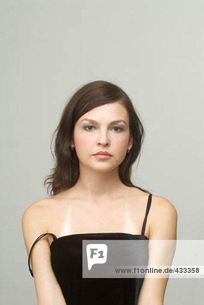 Portrait einer jungen Frau tragen schwarzes Kleid  mit einem Armband rutschte