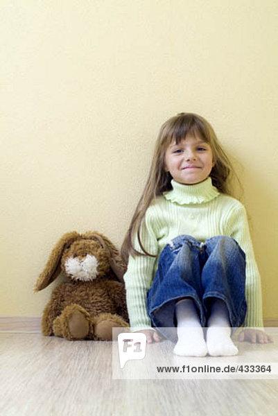 junges Mädchen sitzen auf Boden mit Kuscheltier junges Mädchen sitzen auf Boden mit Kuscheltier
