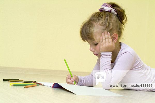 junges Mädchen mit Buntstiften in ihrem Malbuch