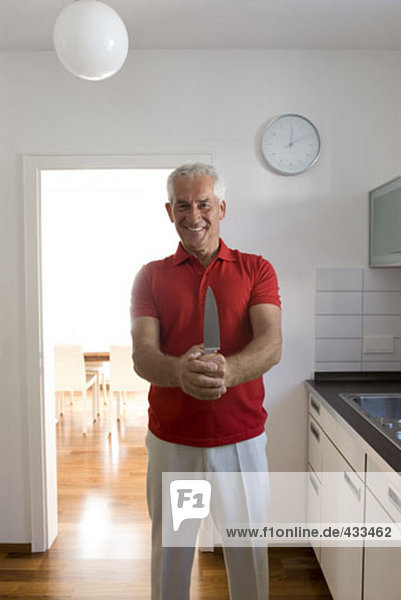 smiling mature man holding knife in kitchen