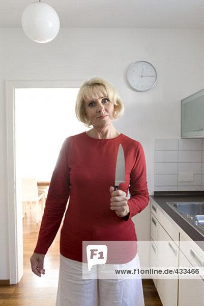 Portrait of reife Frau hält scharfen Küchenmesser