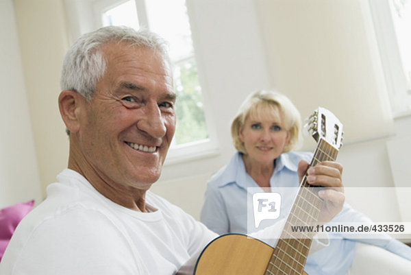 mature couple at home  smiling man with guitar