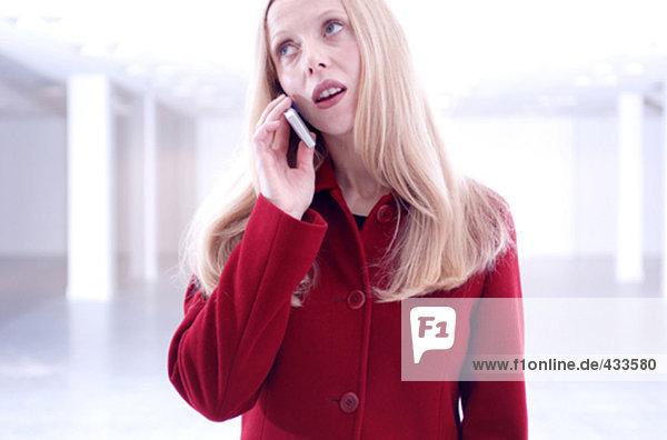 Portrait einer jungen Frau in roten Mantel anhören Handy