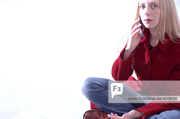 Porträt von Frau im roten Mantel und Jeans mit zellularen Telefon sitzen