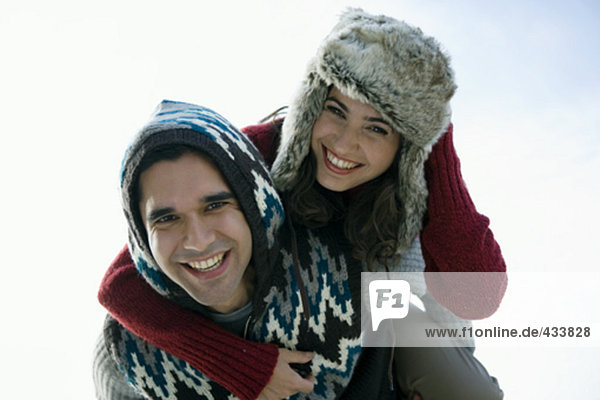 couple in winter clothes playing piggyback