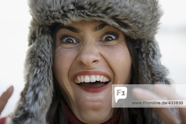 portrait of young woman in winter pulling a funny face