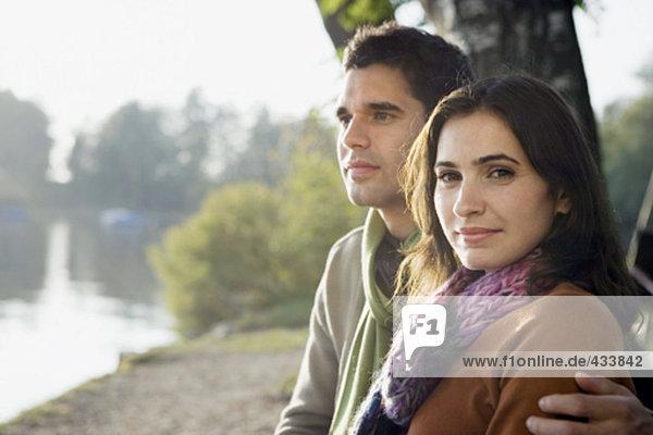 Porträt jungen Paares in Liebe Frau Blick in die Kamera zusammensitzen