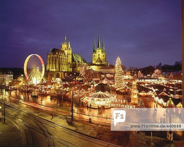 Weihnachtsmarkt in der Abenddämmerung vor der Kirche beleuchtet