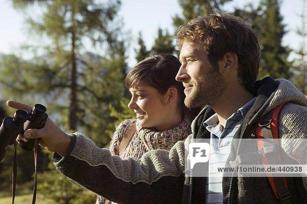 Young couple walking on mountains  man holding binocular