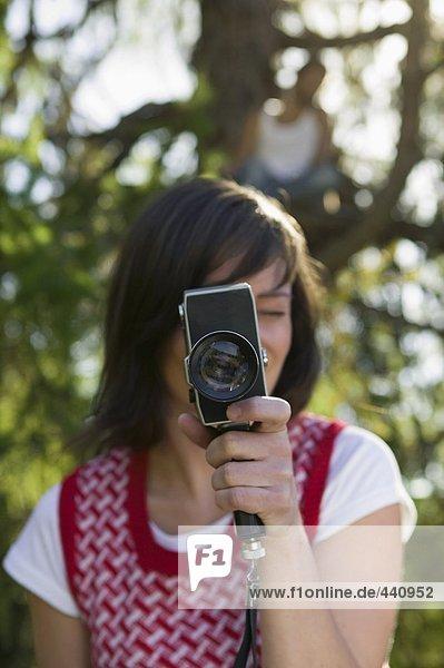 Junge Frau mit Kamera  junger Mann auf Baumhaus sitzend