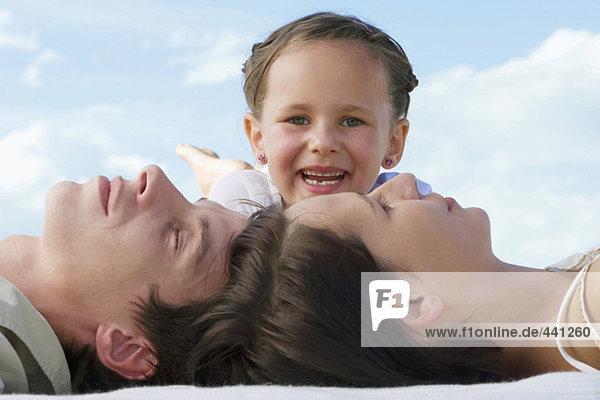 Eltern liegen Kopf an Kopf  Tochter lächelt  Nahaufnahme