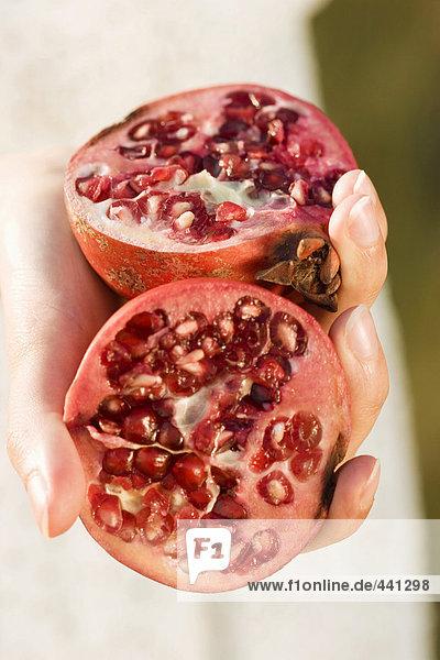 Frau hält Granatapfelhälften  Nahaufnahme