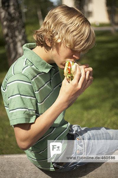 Boy sitting outdoors eating a sandwich.
