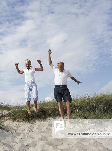 Paar springen nach unten den Sand.