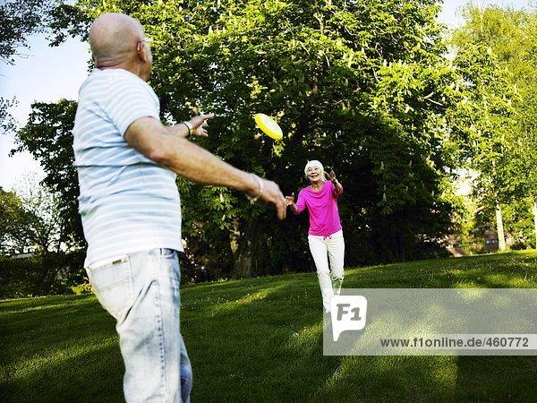 Ein Mann und eine Frau wirft Frisbee.