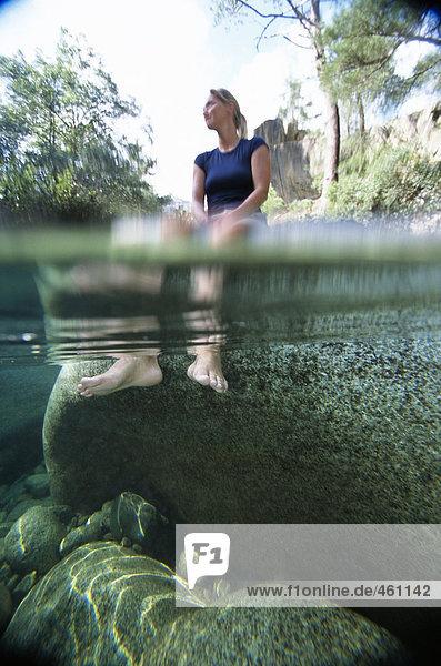 Eine Frau mit ihre Füße im Wasser.