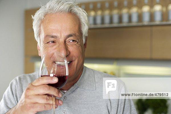 Grauhaariger Mann mit einem Glas Wein in der Hand - Küche - Abendessen - Alkohol  fully_released