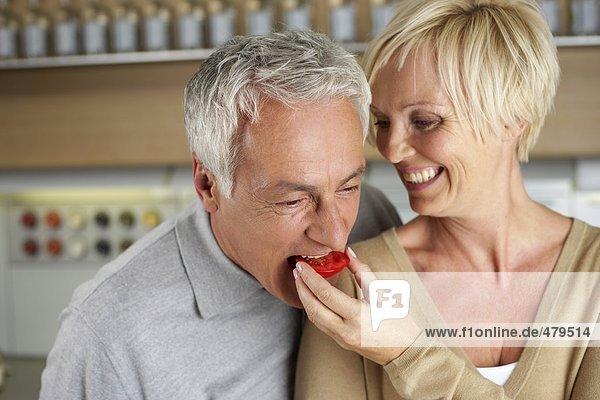 Grauhaariger Mann beißt in eine Tomatenscheibe  die ihm eine blonde Frau hinhält - Kochen - Romantik - Leidenschaft  fully_released