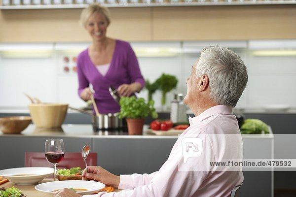 Grauhaariger Mann wird von einer blonden Frau bekocht - Abendessen - Liebe  fully_released