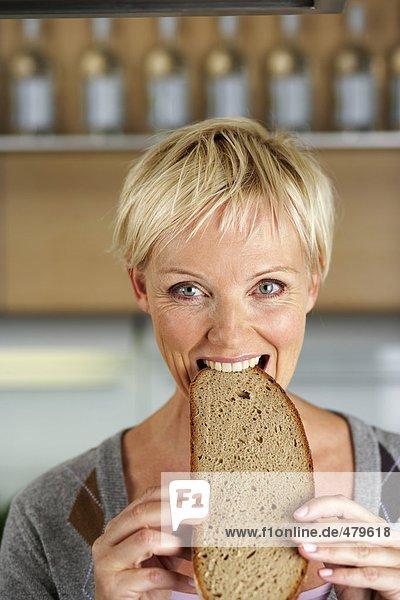 Blonde Frau mittleren Alters beißt in eine Scheibe Brot - Kohlenhydrate - Hunger  fully_released