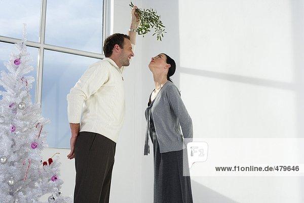 Mann hält einen Mistelzweig über eine Frau  fully_released